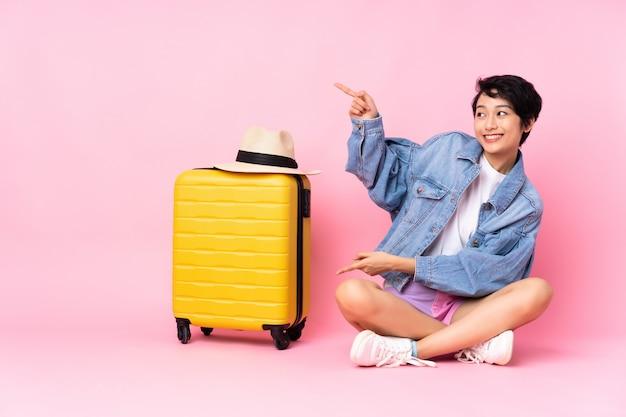 Donna vietnamita del giovane viaggiatore con la valigia che si siede sul pavimento sopra la parete rosa che indica dito il lato Foto Premium