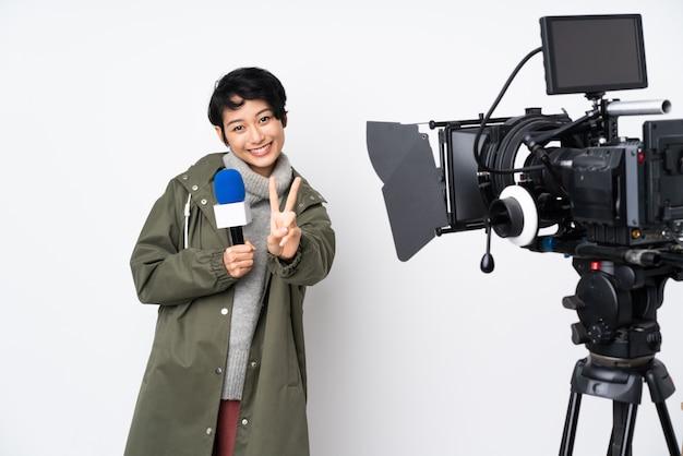 Donna vietnamita del reporter che tiene un microfono e che riferisce le notizie che sorridono e che mostrano il segno di vittoria Foto Premium