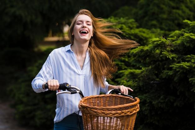 Donna vista frontale in sella alla sua bici Foto Gratuite