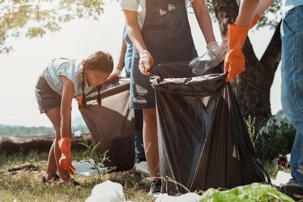 Donna volontaria che prende la plastica dell'immondizia per la pulizia al parco del fiume Foto Premium