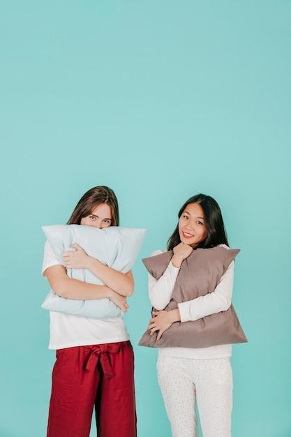 Donne affascinanti che abbracciano i cuscini Foto Gratuite