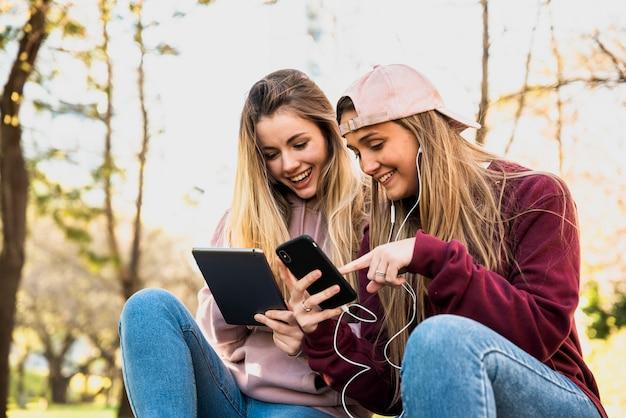 Donne all'aperto nel parco utilizzando i cellulari Foto Gratuite