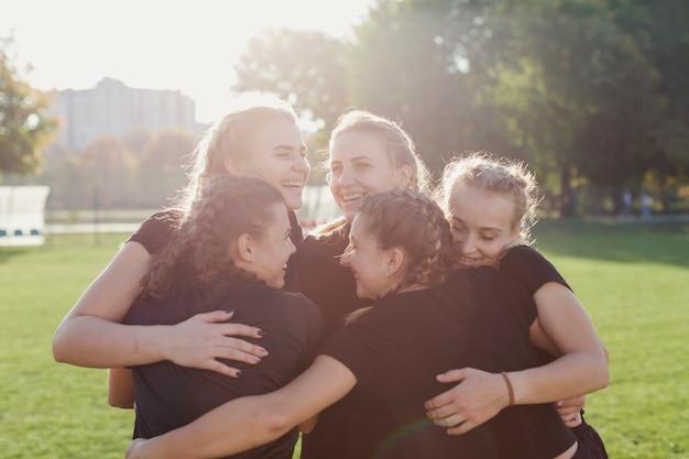 Donne allegre che abbracciano su un campo da calcio Foto Gratuite