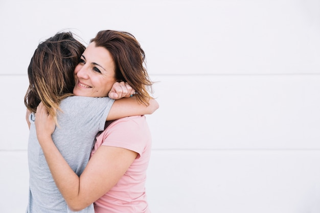 Donne allegre che abbracciano vicino al muro bianco Foto Gratuite