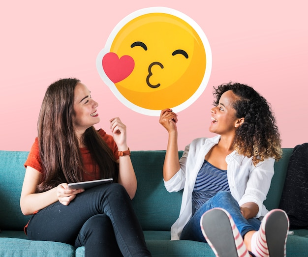 Donne allegre che tengono un'icona dell'emoticon baciante Foto Gratuite