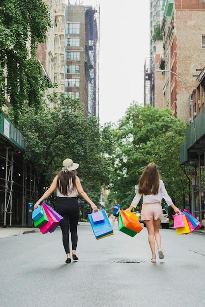 Donne andando su strada con borse della spesa Foto Gratuite