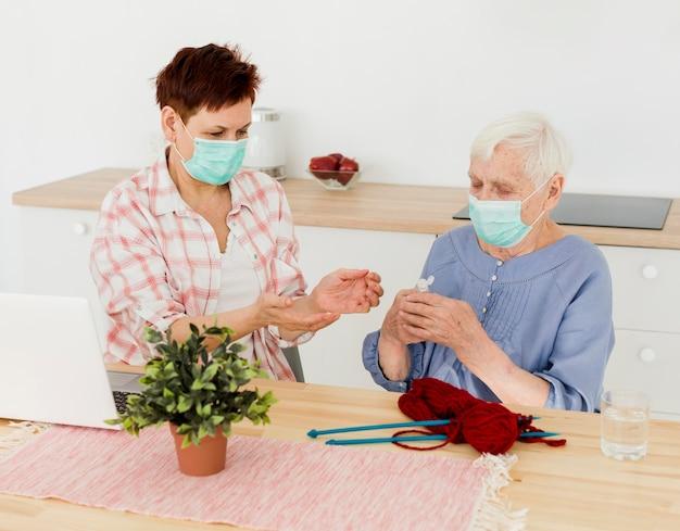 Donne anziane con maschere mediche che si disinfettano le mani mentre lavorano a maglia Foto Gratuite