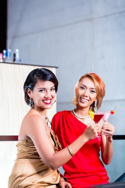 Donne asiatiche che bevono cocktail nella barra di fantasia Foto Premium