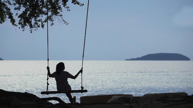 Donne asiatiche che si siedono nelle oscillazioni alla spiaggia durante il tramonto Foto Premium