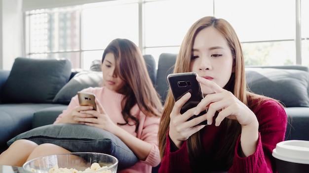 Donne asiatiche che utilizzano smartphone e mangiando popcorn in salotto a casa, gruppo di amico compagno di stanza Foto Gratuite