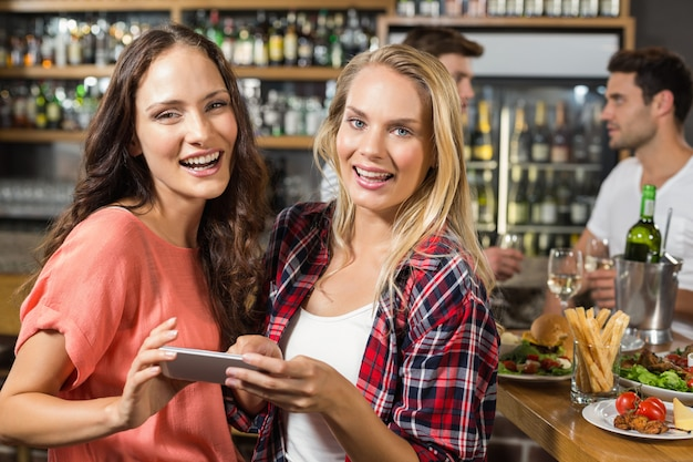 Donne che esaminano macchina fotografica con il telefono in mano Foto Premium