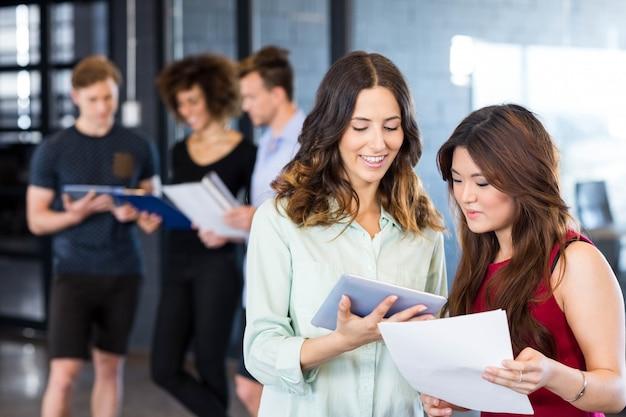 Donne che guardano tablet digitale e avendo una discussione mentre colleghi in piedi dietro in ufficio Foto Premium