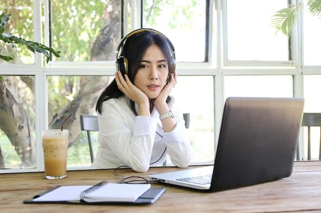 Donne che indicano lo schermo del computer portatile e computer portatile di battitura a macchina dell'uomo sulla tavola di legno, internet delle cose Foto Premium