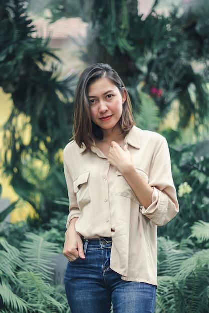 Donne che indossano camicie marroni che posano nel giardino Foto Premium