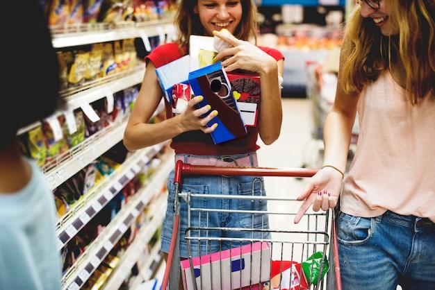 Donne che scelgono il cibo da una mensola del supermercato Foto Premium
