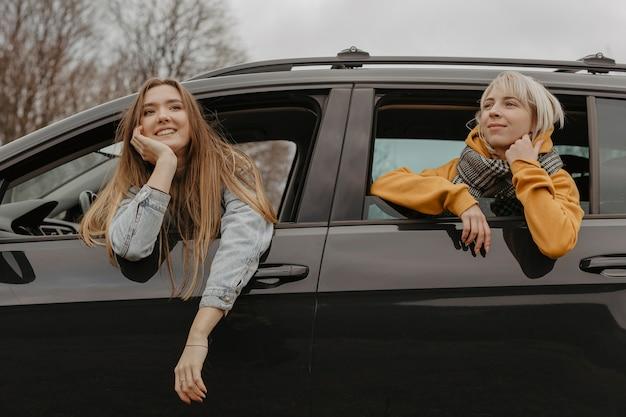 Donne che si rilassano dal finestrino della macchina Foto Gratuite