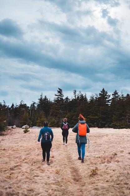Donne che stanno sul campo marrone circondato dagli alberi verdi sotto le nuvole e il cielo blu bianchi Foto Gratuite