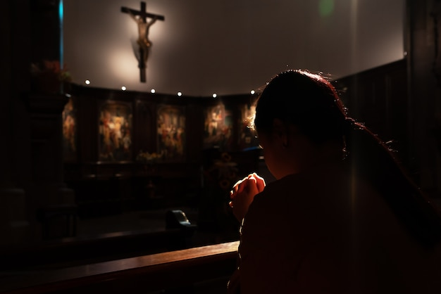 Donne depresse che si siedono nella chiesa della scarsa visibilità e che pregano gesù sulla croce, concetto internazionale di giornata dei diritti umani Foto Premium