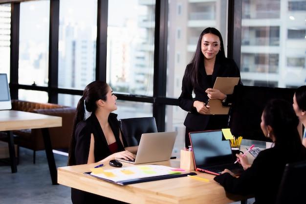 Donne di affari che sorridono e che discutono con il collega nella riunione Foto Premium