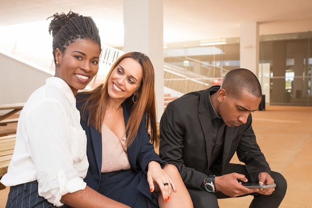 Donne di affari felici che sorridono alla macchina fotografica e uomo che per mezzo del telefono mobile Foto Gratuite