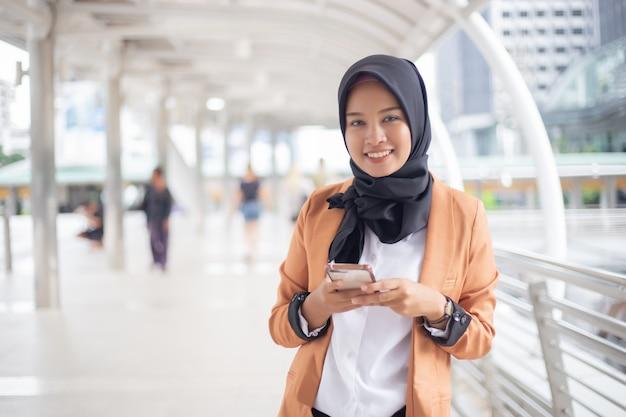 Donne di affari musulmane nel hijab facendo uso dello smartphone nella città. Foto Premium