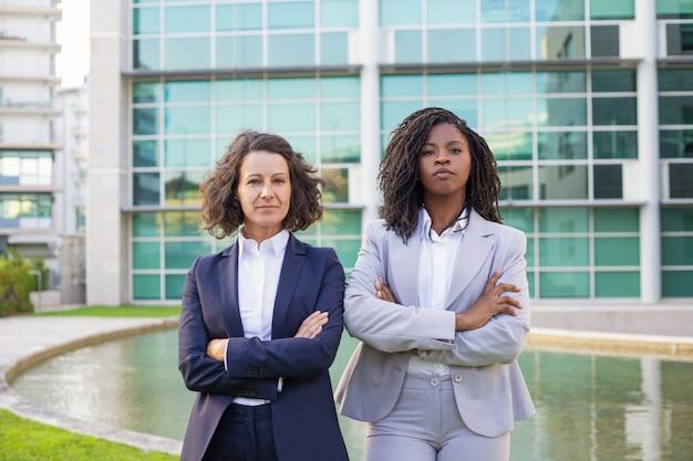 Donne di affari serie sicure che posano con le armi attraversate Foto Gratuite