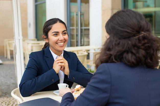 Donne di affari sorridenti che parlano e che bevono caffè Foto Gratuite