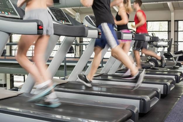 Donne e uomini che corrono su un tapis roulant in palestra Foto Premium