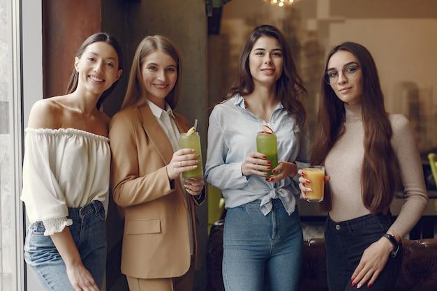 Donne eleganti che stanno in un caffè e che bevono un cocktail Foto Gratuite