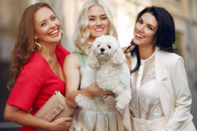 Donne eleganti con cagnolino in una città Foto Gratuite