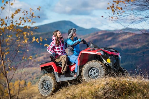 Donne felici che guidano atv sulle colline innevate Foto Premium