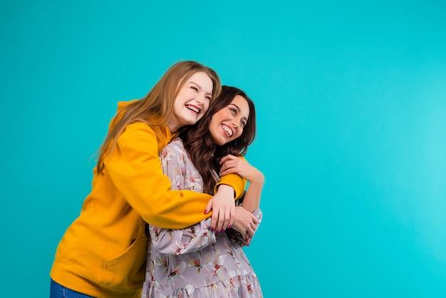 Donne felici che si tengono isolato sopra il fondo del blu di turchese Foto Premium