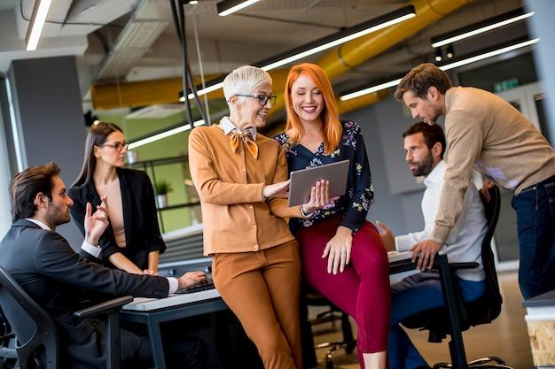 Donne felici di affari che lavorano insieme online su una compressa digitale all'ufficio Foto Premium