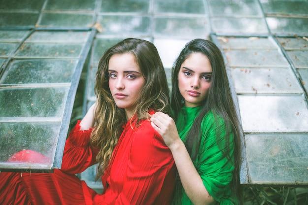 Donne in abiti verdi e rossi che guarda l'obbiettivo Foto Gratuite