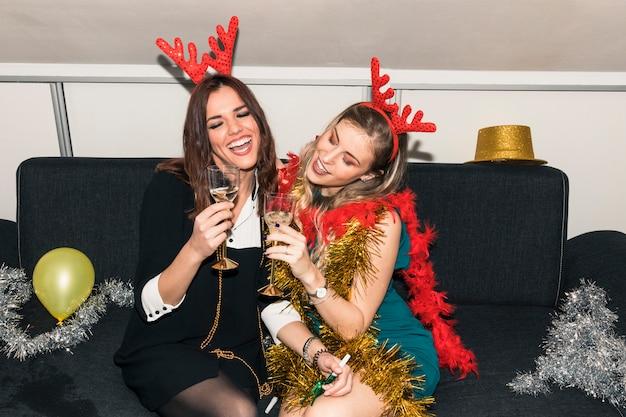 Donne in corna di cervo seduto con bicchieri di champagne Foto Gratuite