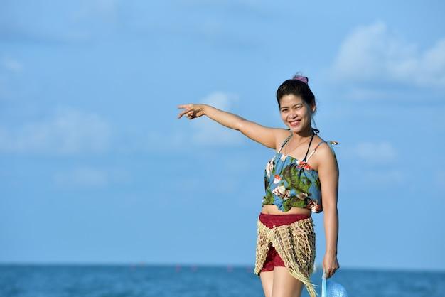 Donne in costume da bagno alla moda che riposa sulla spiaggia di sabbia Foto Premium