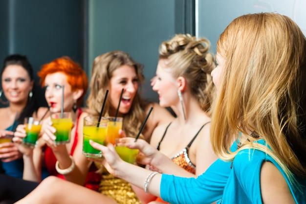 Donne in discoteca o club che bevono cocktail Foto Premium