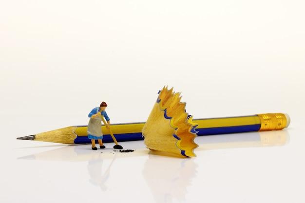 Donne in miniatura che puliscono il residuo di matita. concetto di giorno di pulizia. Foto Premium