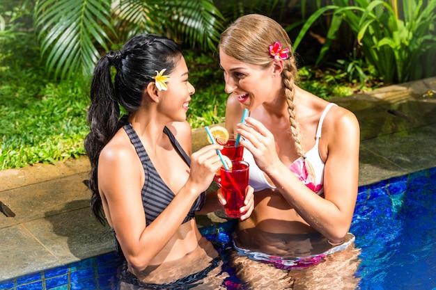 Donne in piscina dell'hotel asiatico che bevono cocktail Foto Premium