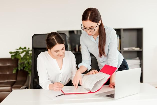 Donne in ufficio che lavorano e firmano documenti commerciali Foto Premium