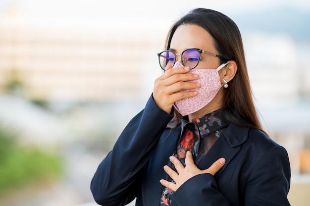 Donne lavoratrici che indossano maschere, tosse e mal di gola a causa di un'infezione da virus Foto Premium