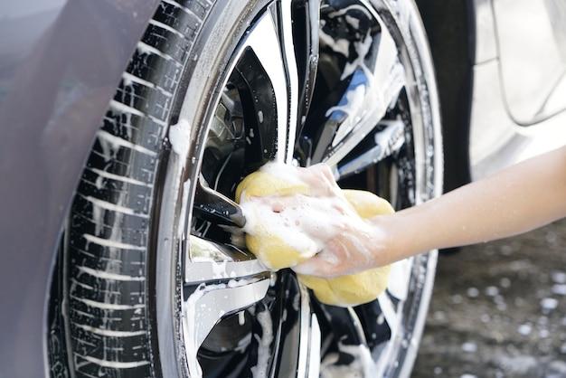 Donne mano con schiuma spugna lavaggio ruota auto Foto Premium