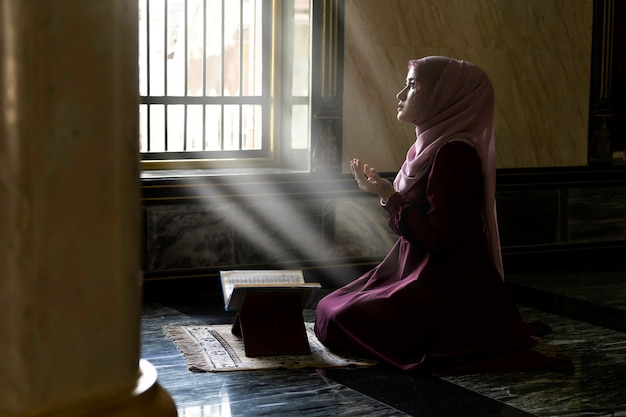 Donne musulmane che indossano camicie viola facendo preghiera dell'islam. Foto Premium