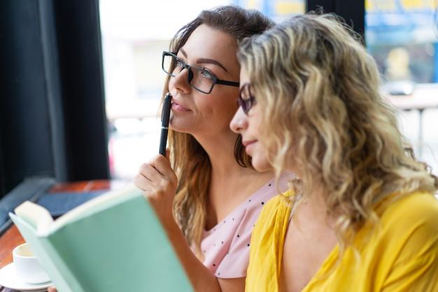 Donne pensierose che leggono manuale nel caffè Foto Gratuite
