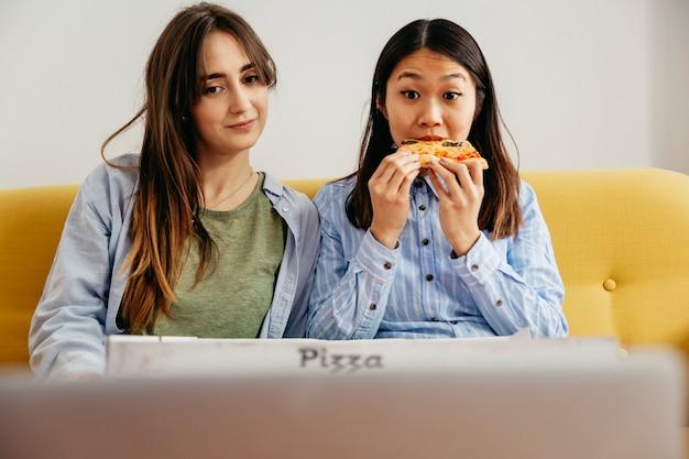 Donne rilassate che mangiano pizza con il film Foto Gratuite