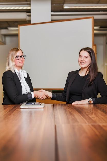 Donne sedute al tavolo stringendo la mano sorridente Foto Gratuite