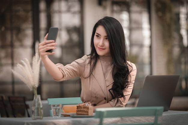 Donne sedute rilassante selfie e sorridente su smartphone e laptop sul tavolo Foto Premium