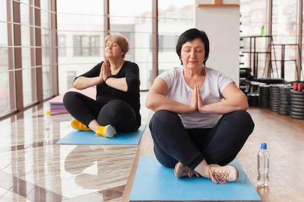 Donne senior in palestra che fanno yoga Foto Gratuite