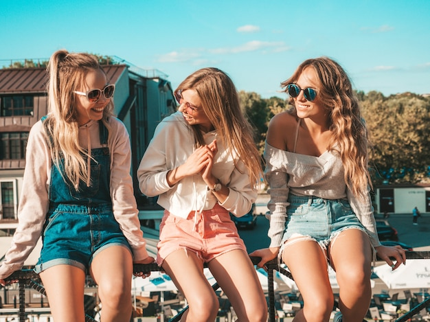 Donne sexy che si siedono sul corrimano in strada comunicano e discutono di qualcosa Foto Gratuite
