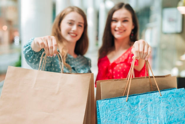 Donne sfocate che mostrano borse Foto Gratuite